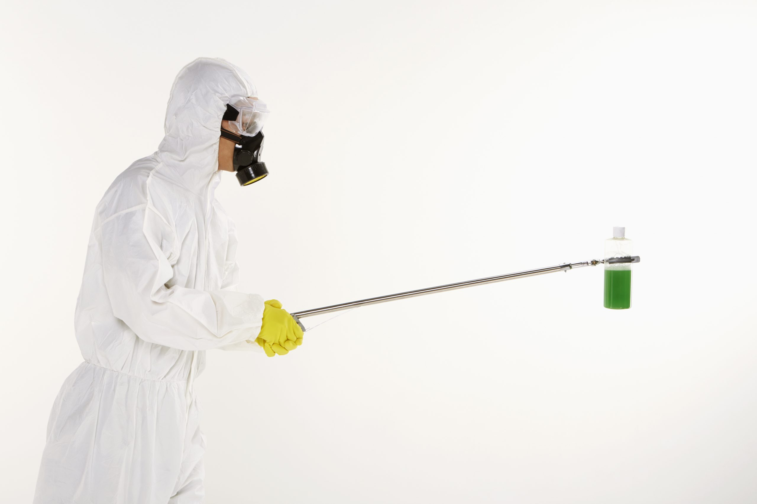 Man in protective suit holding up a bottle of chemical hazardous waste